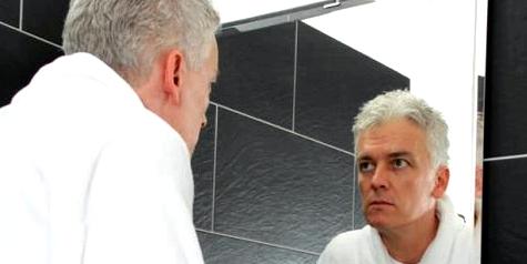 Mann in Wechseljahren vor dem Spiegel