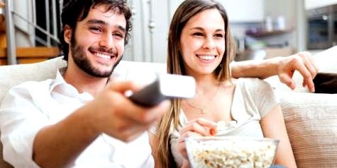 Ein Pärchen sieht fern und isst Popcorn