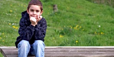 Junge mit ADHS sitzt im Grünen