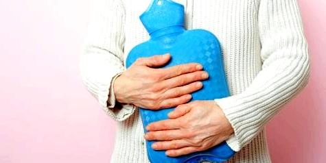 Frau wärmt sich mit Wärmflasche den Bauch