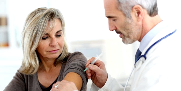 Eine Frau wird von einem Arzt geimpft