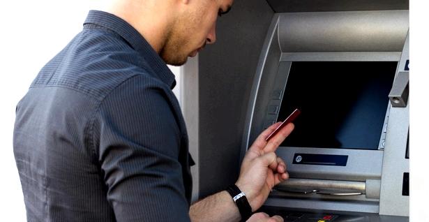Ein Mann hebt Geld am Automaten ab