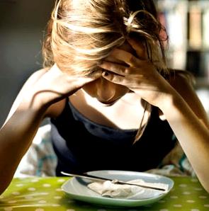 Frau starrt auf leeren Teller