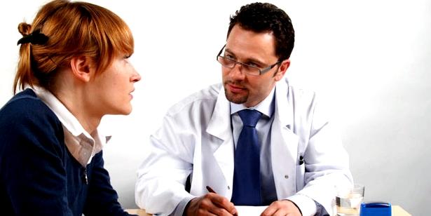 Gynäkologe und Frau reden über Menstruationsbeschwerden