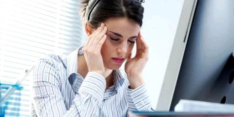 Frau mit Kopfschmerzen vor Computer