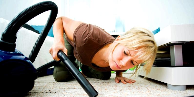 Frau reinigt Teppich