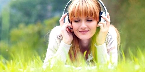 Eine Frau hört Musik auf einer Wiese