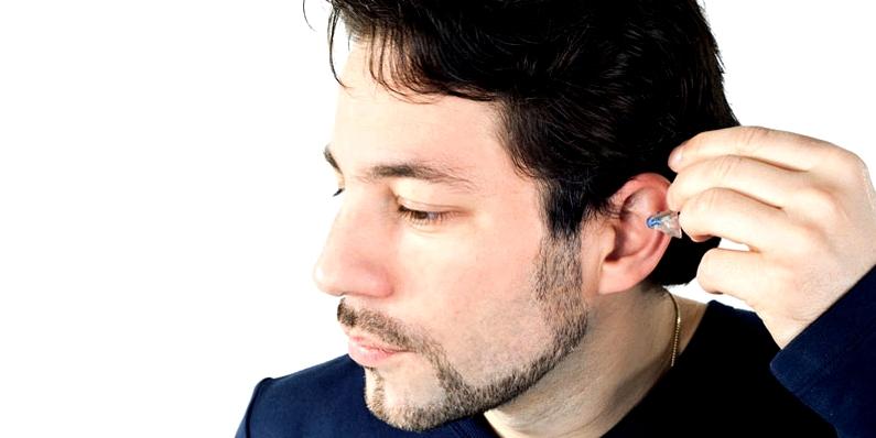 Mann setzt Masker zur Tinnitus-Behandlung ein