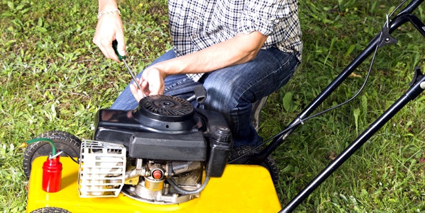 Ein Mann repariert einen Rasenmäher