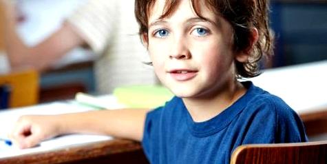 Ein Junge sitzt auf der Schulbank